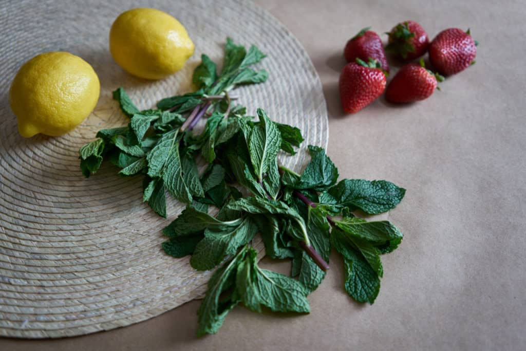 Fresh mint, lemons, and strawberries on a woven placemat.