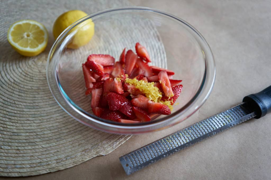 A glass bowl filled with sliced strawberries and lemon zest sits on a woven placemat. A zester is in the foreground and lemons are in the background.