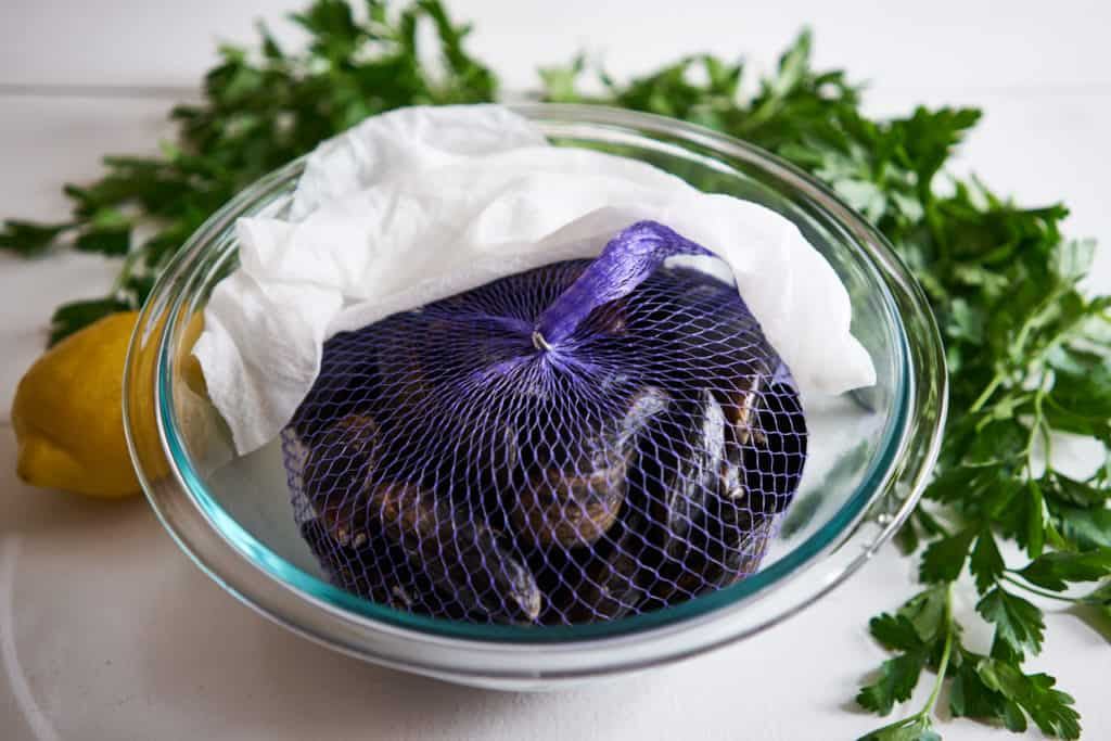 PEI mussels in a purple net sit in a glass bowl with a damp paper towel pulled back. Parsley and a lemon are in the background on a white surface.