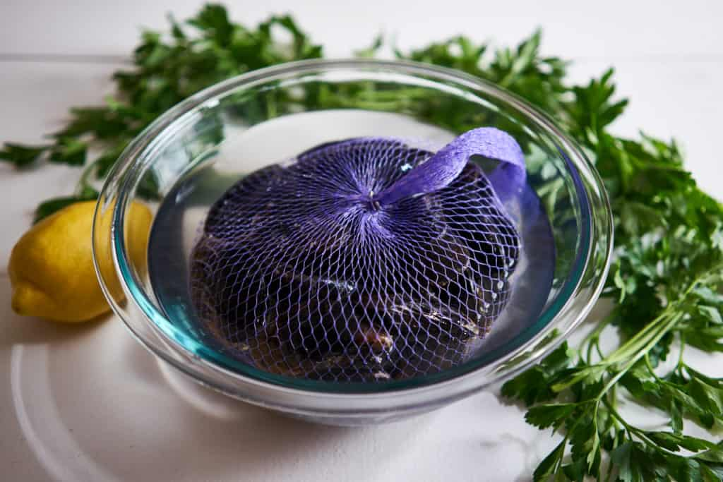 PEI mussels in a purple net sit in a glass bowl filled with water. Parsley and a lemon are in the background on a white surface.