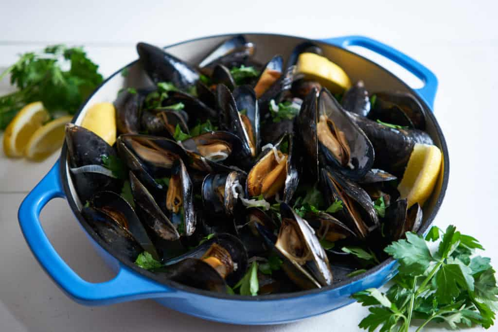 Cooked PEI mussels in white wine in a blue casserole dish. Parsley and lemon wedges surround it on a white surface.