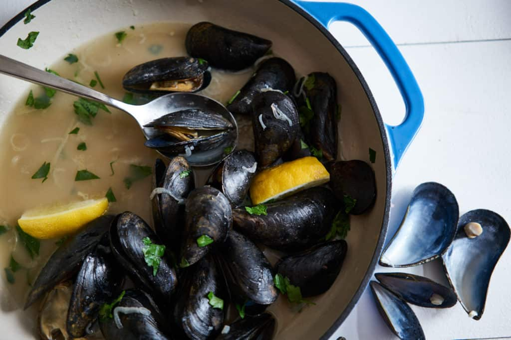 A blue casserole dish with mussels in white wine sauce (moules marinières) and lemon wedges sits on a white surface with empty mussel shells to the right of the dish.