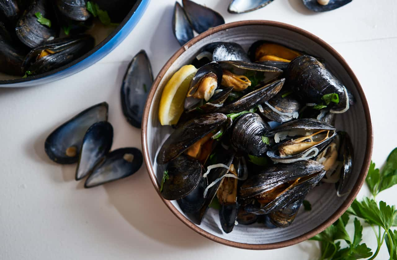 A bowl of mussels in white wine (moules marinières) on a white surface surrounded by parsley and empty mussel shells. A blue bowl of cooked mussels is in the upper left corner.