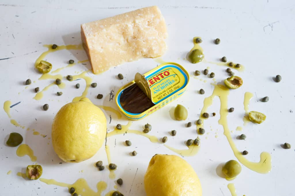 A can of Cento anchovies that is slightly open, surrounded by a block of parmigiano reggiano cheese, green olives, capers, and two lemons. They all sit on a white surface that has been drizzled with olive oil.
