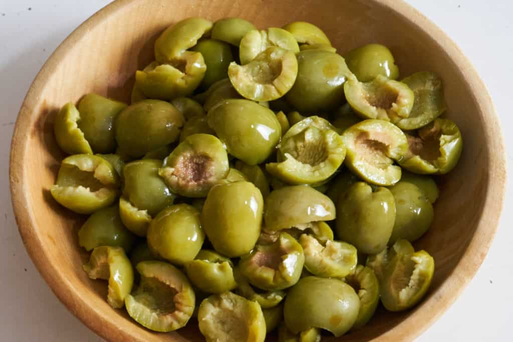A wooden bowl full of Castelvetrano olives that have been torn in half.