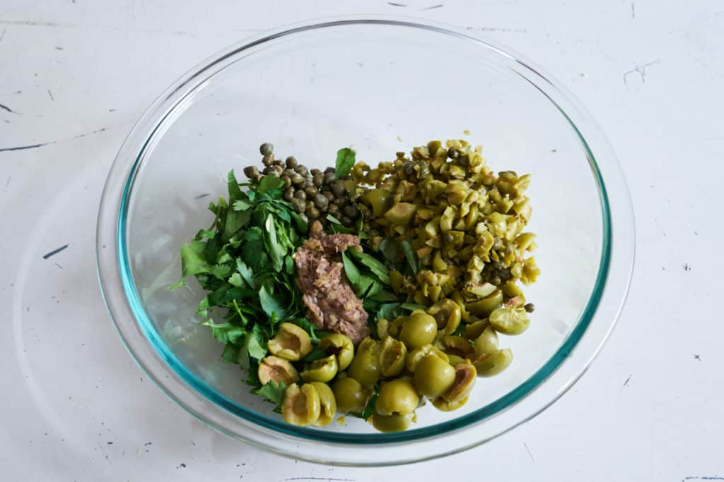 A glass bowl with fresh Italian herbs, green olives, capers, and anchovy-garlic paste.