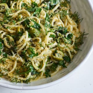 Linguine pasta with green olives, herbs, and capers topped with bread crumbs in a white bowl sitting on a white surface.