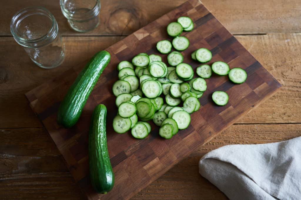 Sliced Persian cucumbers and two whole Persian cucumbers on a wooden cutting board.