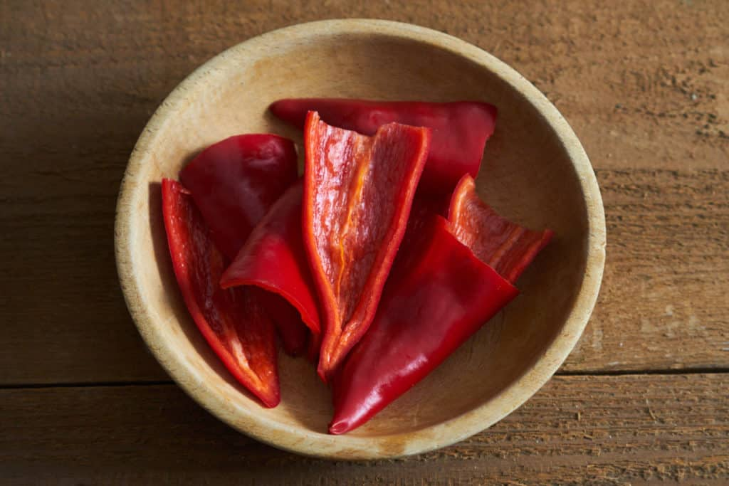 Red Fresno chiles, sliced in half and seeds removed, in a wooden bowl.