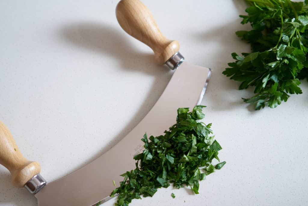 A mezzaluna with wooden handles, chopped parsley, and a bundle of fresh parsley on a white surface.