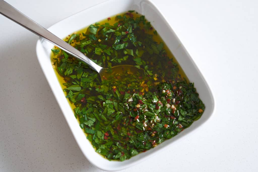 Chimichurri sauce in a white rectangular bowl with a spoon in it.