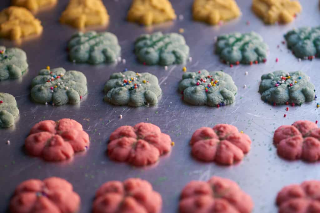 Red, blue, and green Spritz cookies of various shapes on a baking sheet.