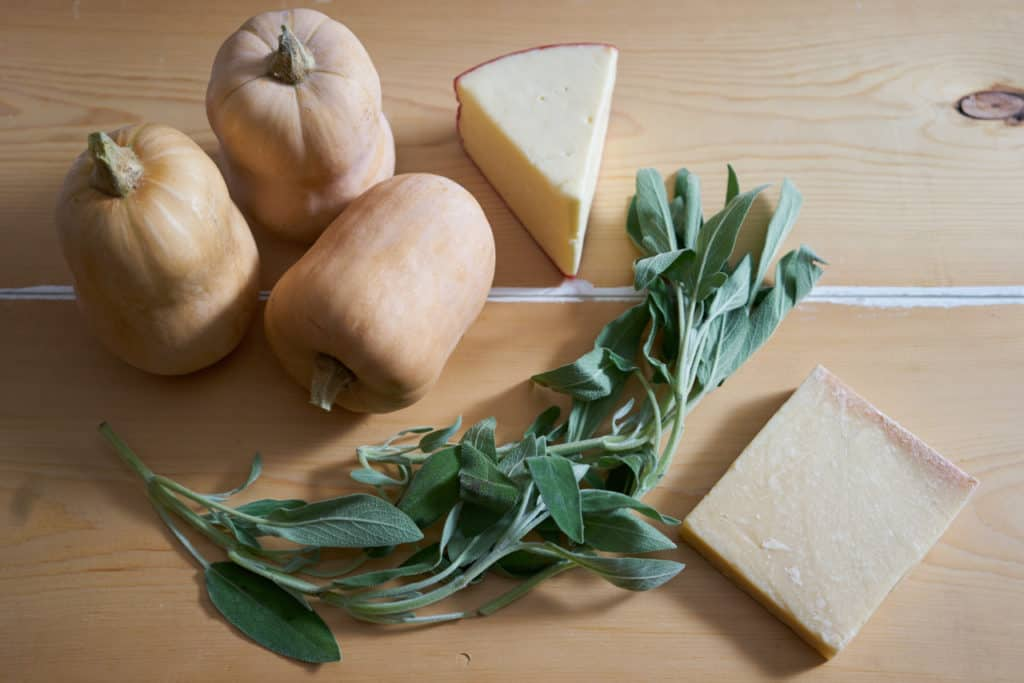 Three butternut squash, fresh sage, fontina and parmigiano cheese on a natural wood surface.
