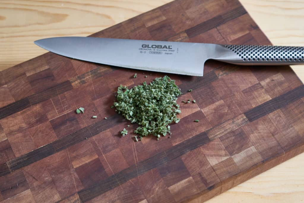 A chef's knife on a wooden cutting board beside chopped fresh sage.