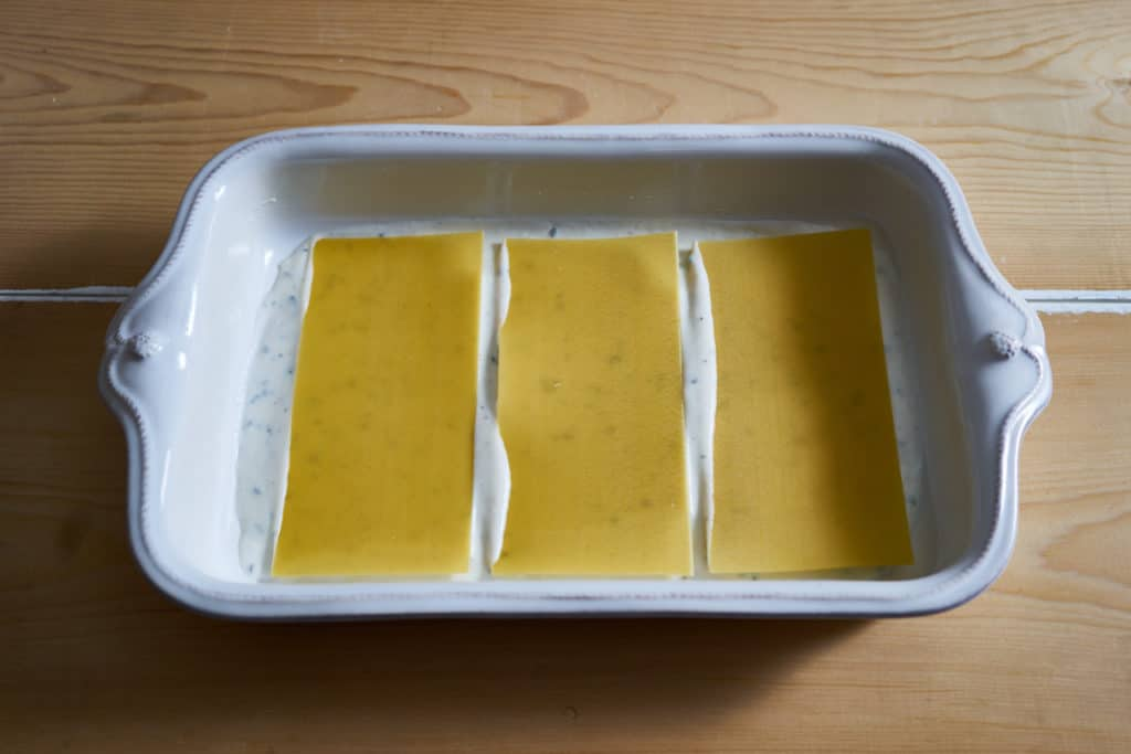 Bechamel sauce and no-boil noodles in a baking dish - the first layer for making butternut squash lasagna.