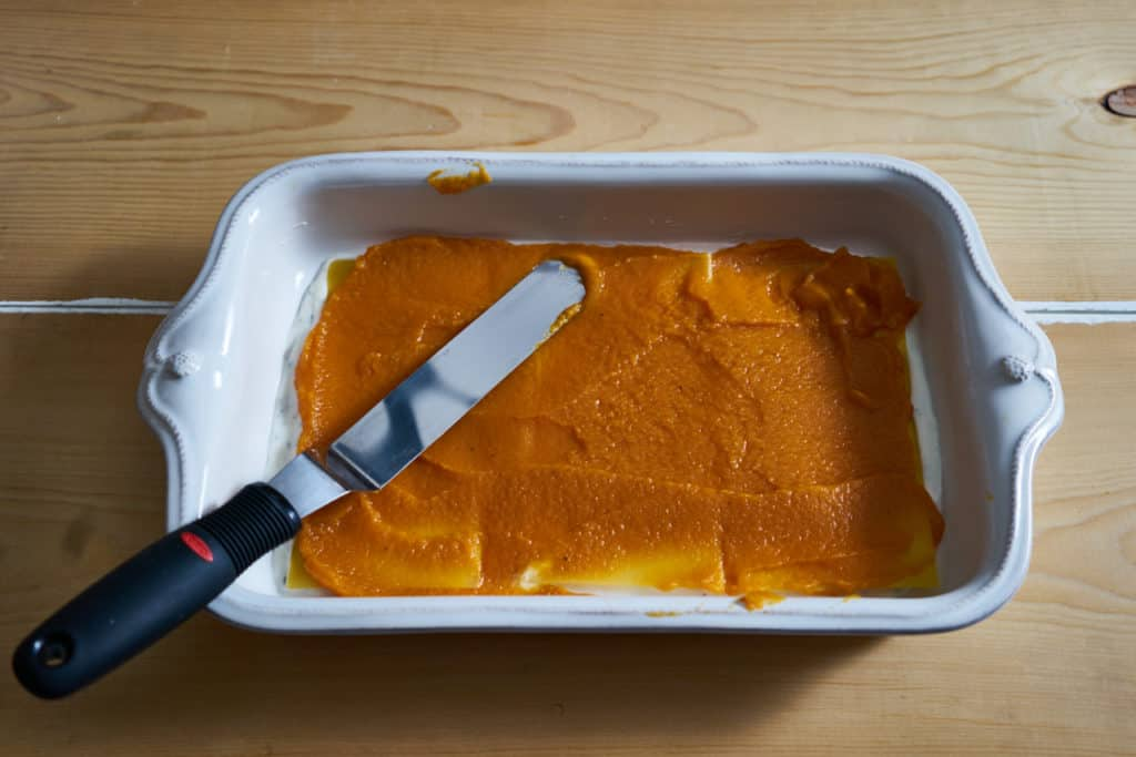 Butternut squash puree is spread on top of lasagna noodles in a white baking dish with an offset spatula.