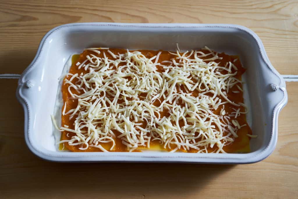 A layer of grated cheese is added to butternut squash lasagna.