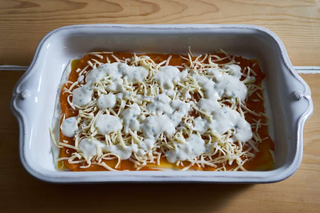 A layer of bechamel sauce is added to butternut squash lasagna in a white baking dish on a wooden surface.