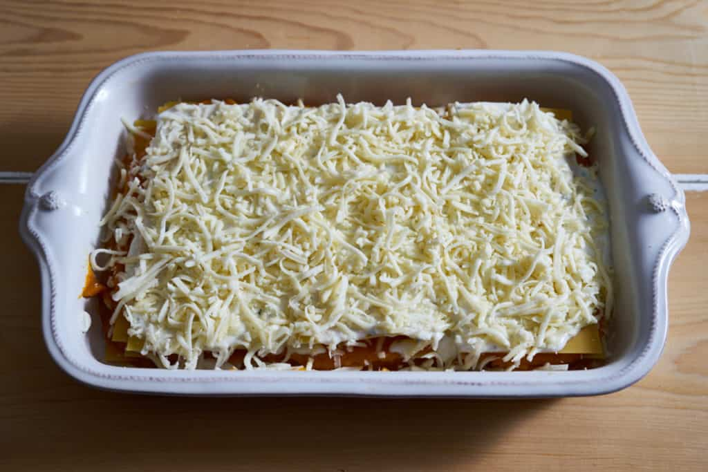 The final layer of cheese is added to butternut squash lasagna prepared in a white baking dish.