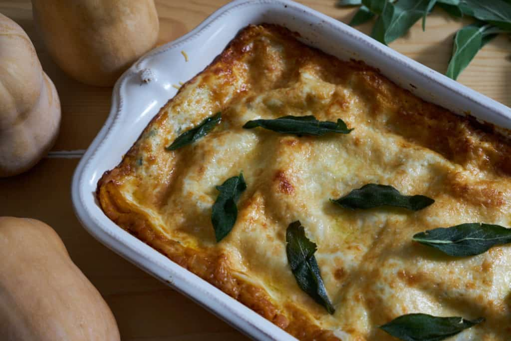 A white baking dish with butternut squash lasagna topped with fried sage surrounded by fresh sage and whole butternut squash.