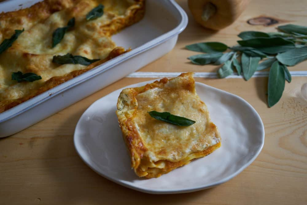 A slice of butternut squash lasagna on a white plate, garnished with a sage leaf. A baking dish filled with lasagna, fresh sage, and a butternut squash are in the background.