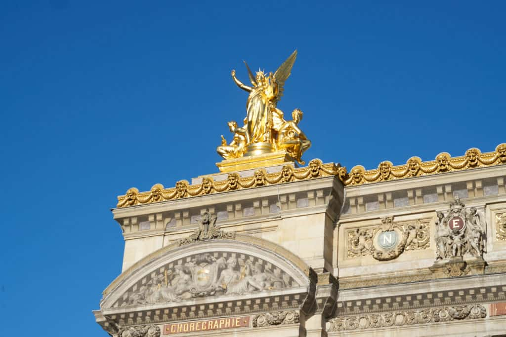 A golden statue of an angel on top of the Palais Garnier - the Paris Opera House.