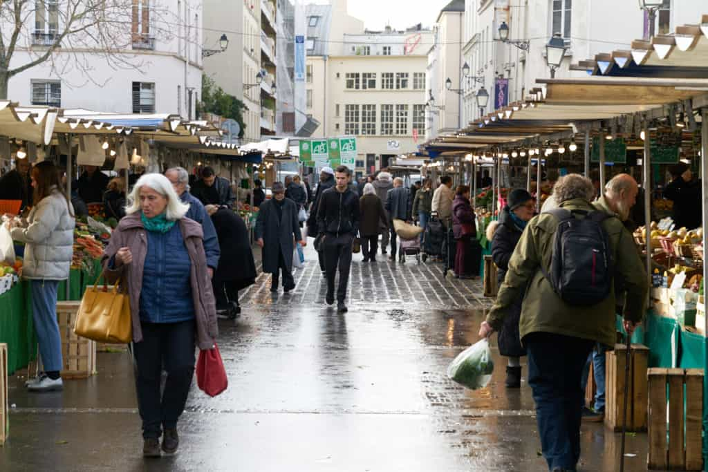 A street full of vendors and shoppers at the Marché d'Aligre in Paris.