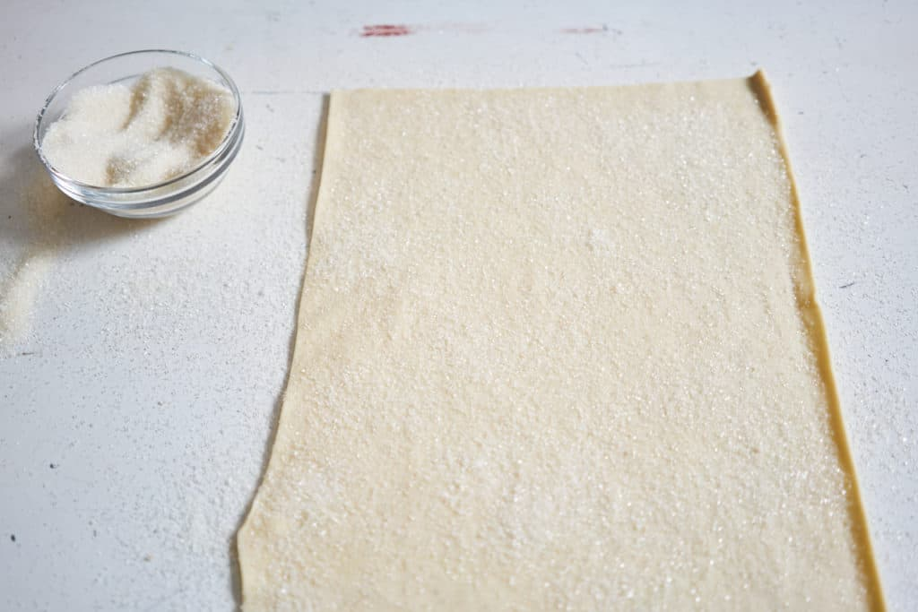 A sheet of puff pastry covered in sugar on a white surface. A bowl of sugar sits on the left.