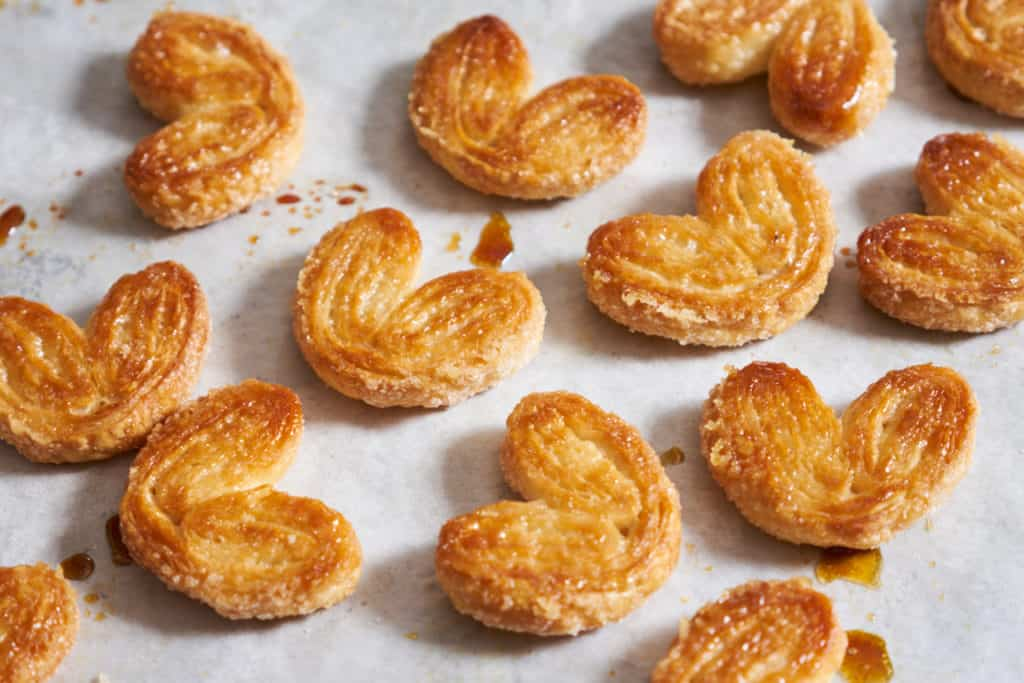 Sweet palmiers made of puff pastry on parchment paper with drops of caramelized sugar.