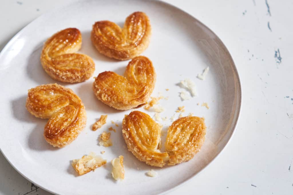 A white plate with palmiers, one is broken and crumbs are strewn over the plate.