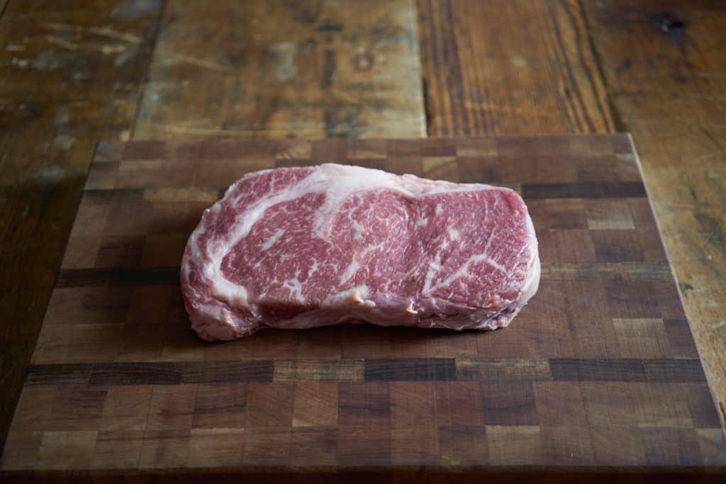 Raw ribeye steak on a wooden cutting board.