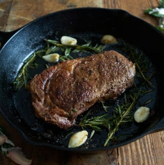 Ribeye steak in a cast iron skillet with rosemary and garlic.