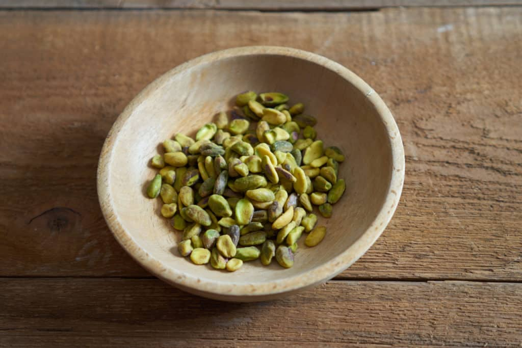 A small wooden bowl of raw pistachios on a wooden surface.