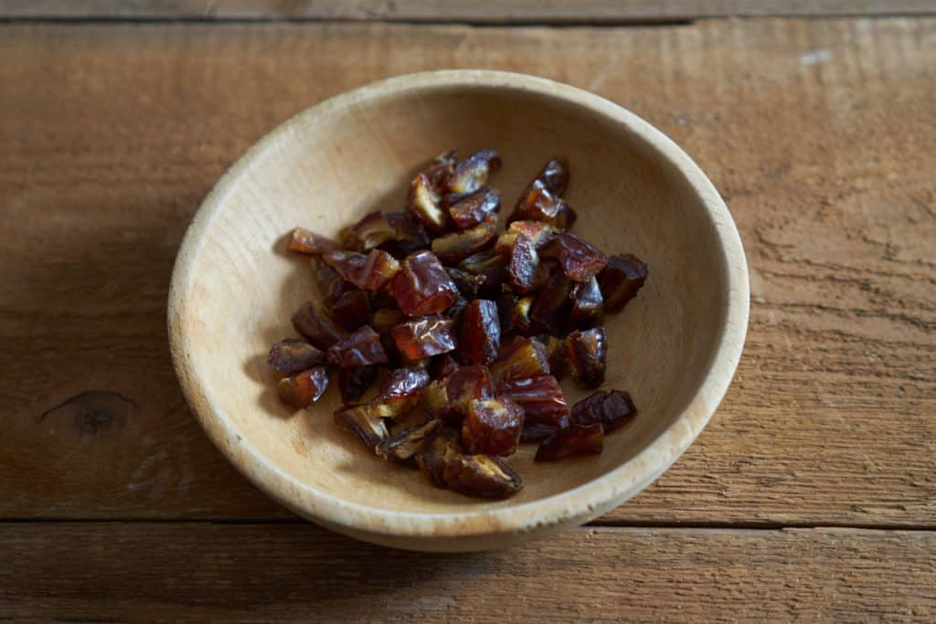 A small wooden bowl of chopped dates on a wooden surface.