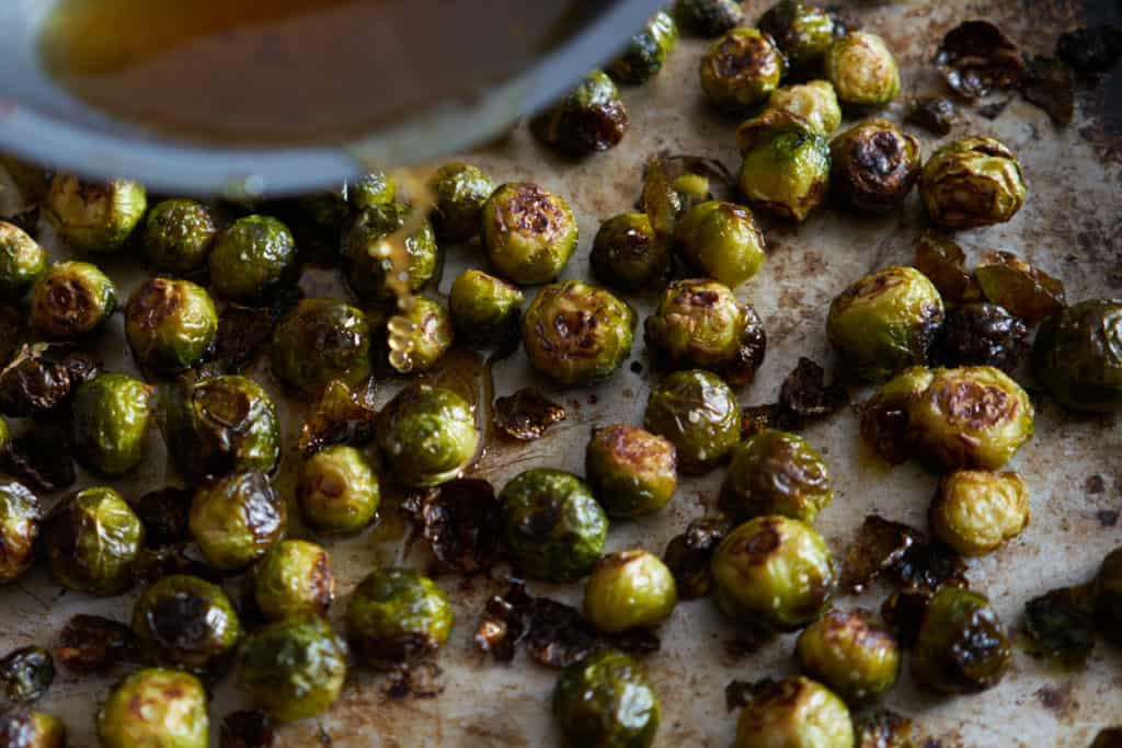 Honey-lime syrup is being poured from a skillet onto roasted brussels sprouts on a baking sheet.