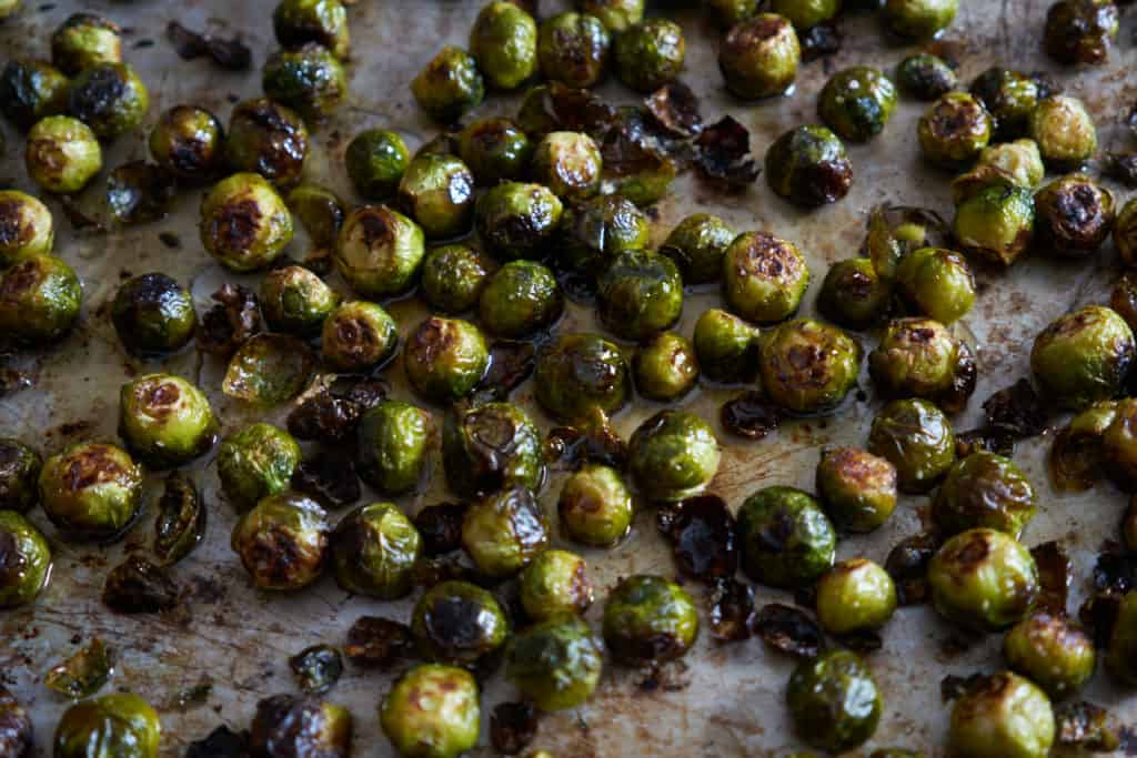 Roasted brussels sprouts coated with a honey-lime syrup on a baking sheet.