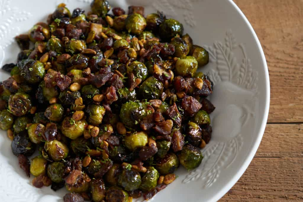Roasted brussels sprouts with pistachios, dates, and lime in a white serving bowl on a wooden surface.