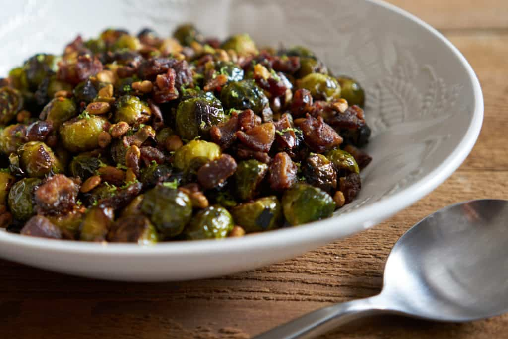 Roasted brussels sprouts with pistachios, dates, and lime in a white serving bowl on a wooden surface. A metal spoon is next to the bowl.