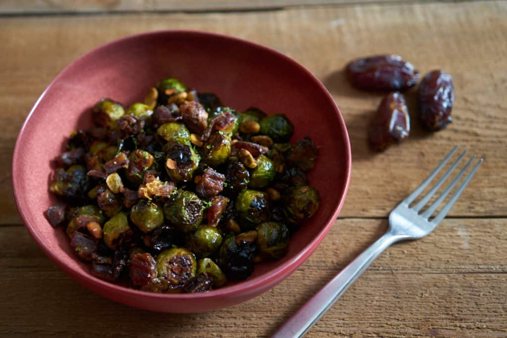 Roasted brussels sprouts with pistachios, dates, and lime in a red serving bowl on a wooden surface. A fork and a few whole dates are next to the bowl.