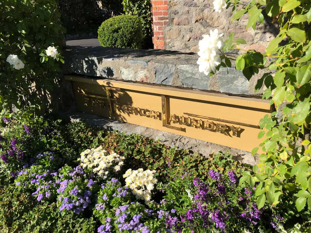 The French Laundry sign in front of the restaurant in bright sunlight.