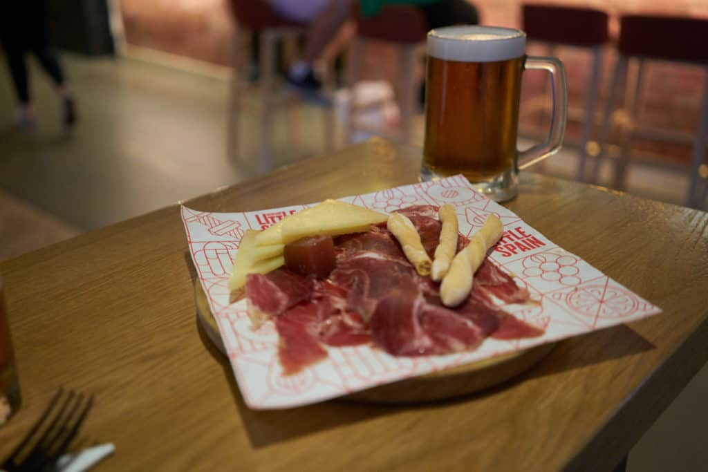 A plate of jamón iberico and manchego cheese with breadsticks on a table with a beer in the background.
