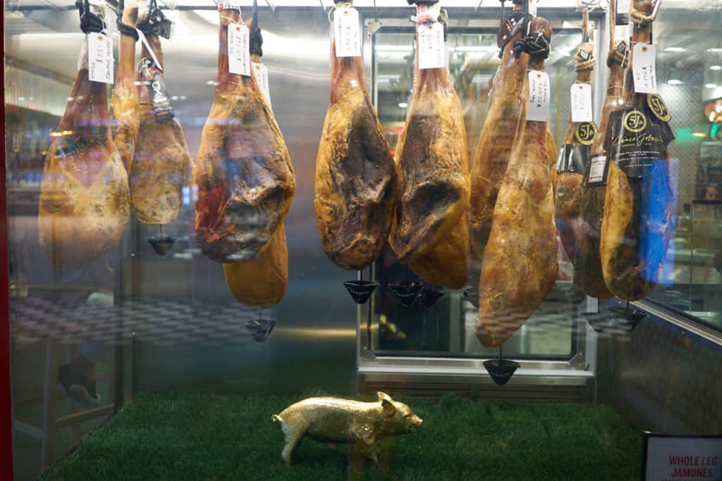 Spanish hams hanging in a case at Mercado Little Spain in NYC.