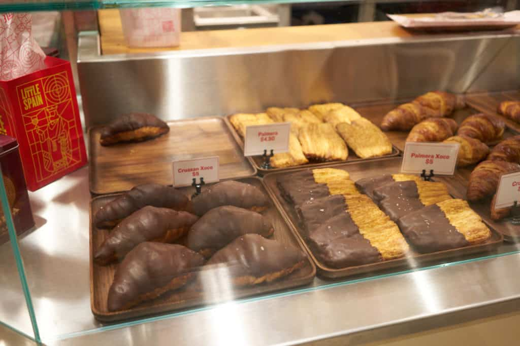 Chocolate covered croissants and other baked goods in a bakery case.