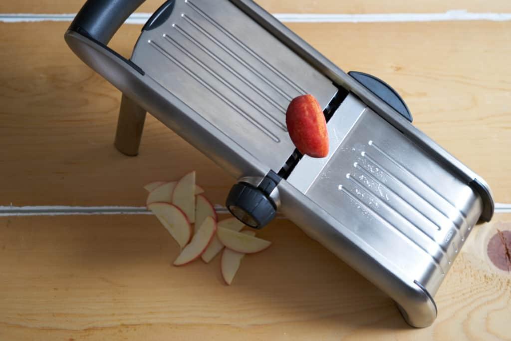 A kitchen mandoline is shown cutting apples.