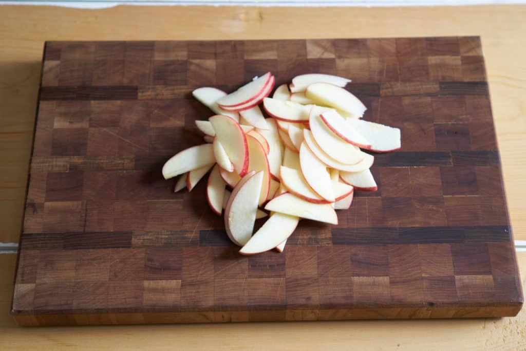 Thinly sliced apples on a wooden cutting board.