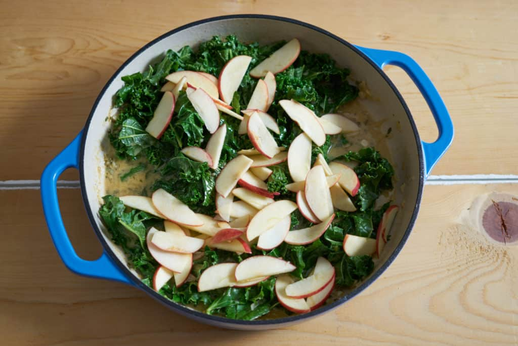 A blue enameled casserole dish with mustard sauce, chopped kale and apples.