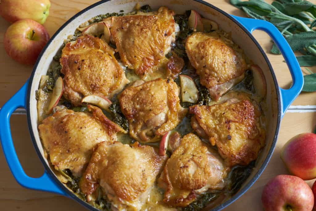 A blue casserole dish containing dijon chicken thighs with apples and kale is on a wooden surface, surrounded by whole apples and fresh sage leaves.