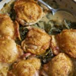 A blue casserole dish containing dijon chicken thighs with apples and kale is on a wooden surface with a silver spoon resting in the sauce.
