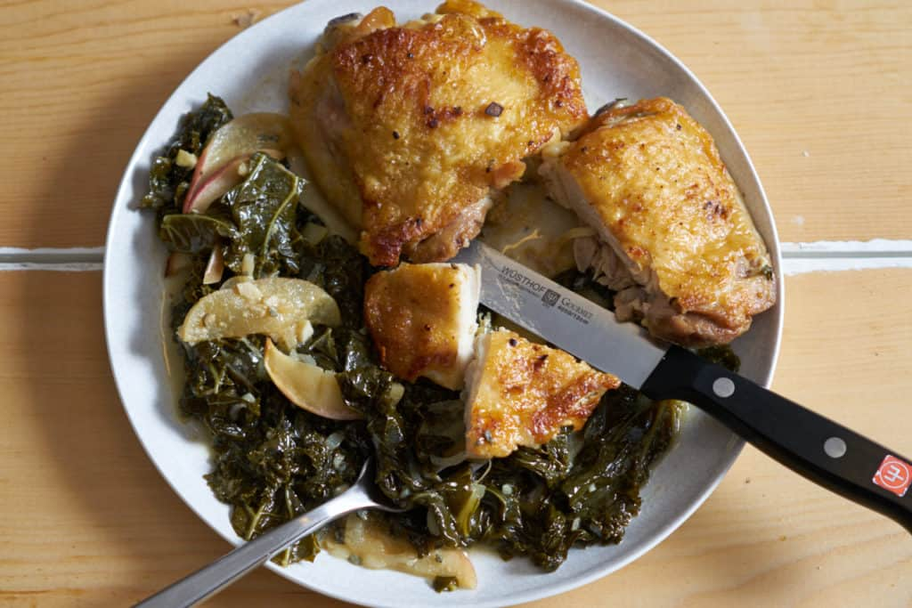 A small round, white plate with two cooked chicken thighs alongside cooked kale and apples in mustard sauce, a knife and fork are on the plate and have been used to prepare a bite.