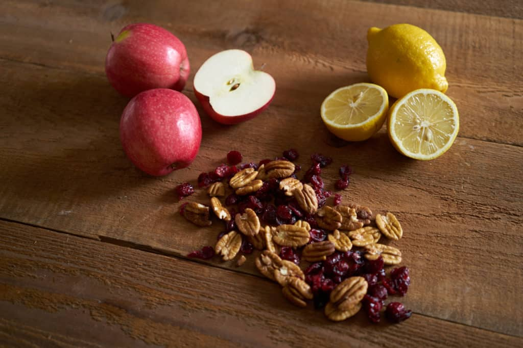 Apples, lemons, pecans and dried cranberries on a wooden surface.